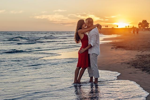 Pár bozkávajúci sa na pláži pri západe slnka