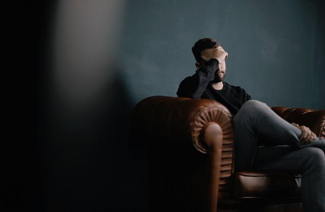 Muž sediaci na gauči sa drží za hlavu.jpg
