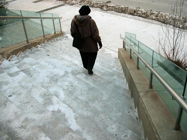 Vonkajšie schodisko, staršia žena ide po schodoch, sneh, zima.jpg