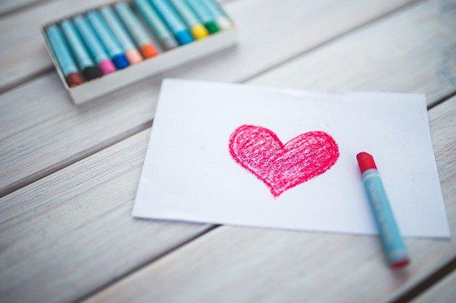 Červené srdce nakreslené pastelkou na bielom papieri.jpg