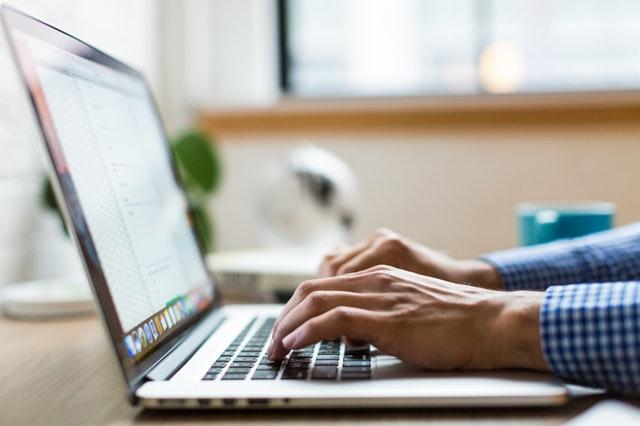Muž v modrej kockovanej košeli píše na notebooku